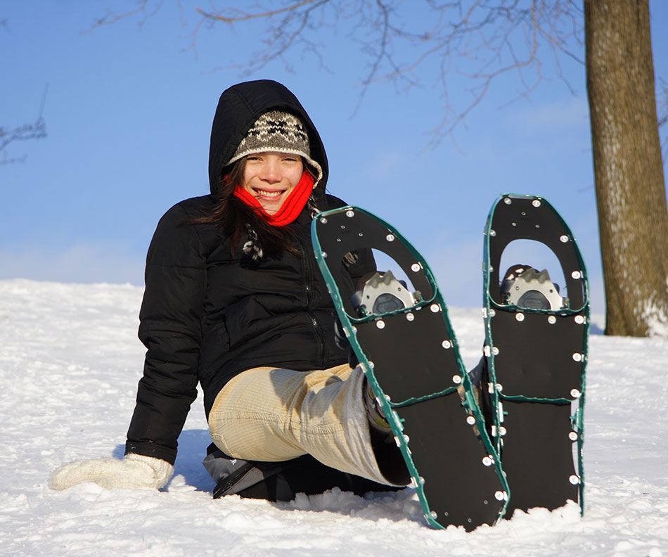 a woman takes a rest while snowshoeing