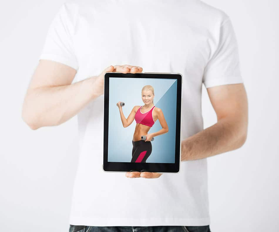 a man holds a tablet used to stream exercise apps